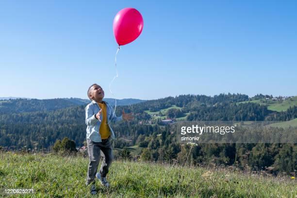 junge löst ballon in blauem himmel - loslassen aktivitäten und sport stock-fotos und bilder