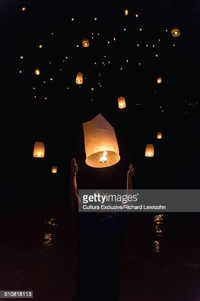 Boy releasing chinese lanterns on New Year's Eve, Krabi, Thailand, Southeast Asia