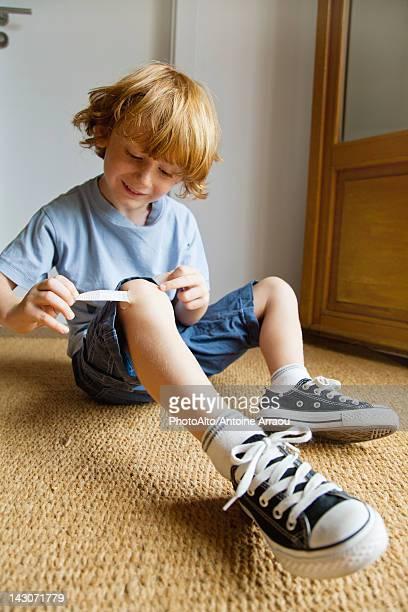 Boy removing adhesive bandage from knee