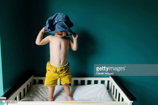 Boy removing shirt while standing in bunkbed against wall