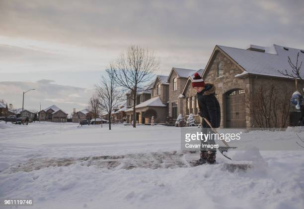 boy removing snow using shovel against houses - inconvenience stock pictures, royalty-free photos & images