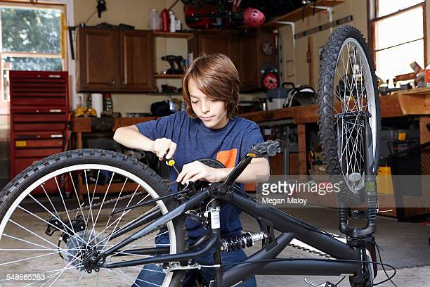 Boy repairing bicycle in garage