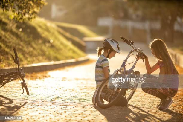 boy repairing his bicycle in bike lane - miljko stock pictures, royalty-free photos & images