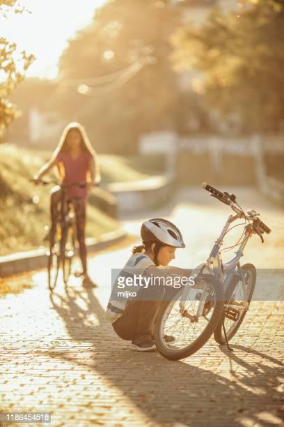 chico reparando su bicicleta en carril bici - 10 11 años fotografías e imágenes de stock