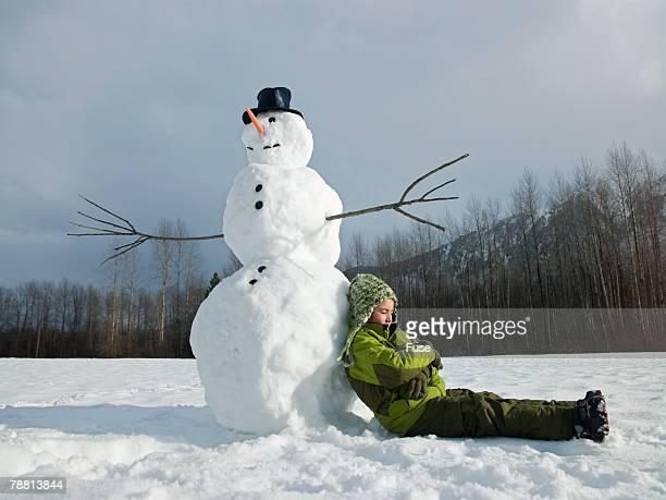 Boy Resting by Snowman