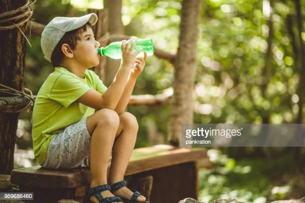 少年の森のボトルから水を飲んでベンチで休んで