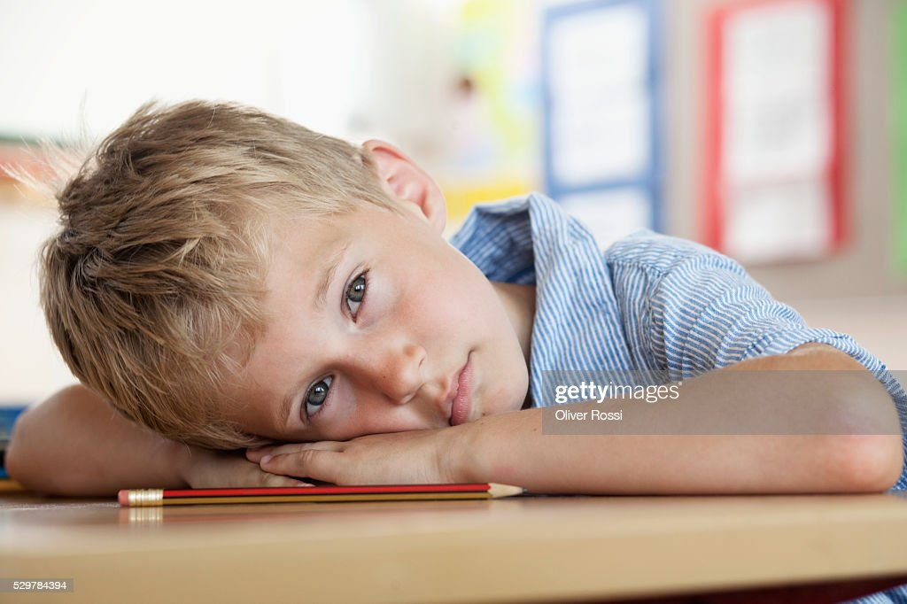 Boy resting on desk in classroom : ストックフォト
