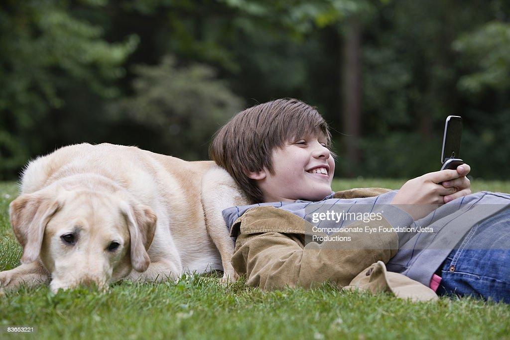 Boy resting on his dog, texting : Stock Photo