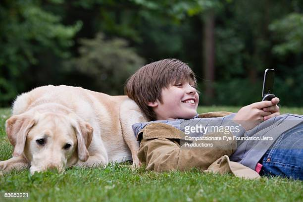 Boy resting on his dog, texting