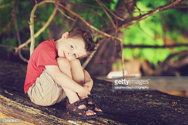Boy resting with his head on his knees
