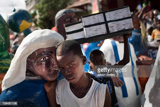 A boy rests against the papier mache figure he has been wearing in a parade during carnival weekend on February 27 2011 in Jacmel Haiti This year's...