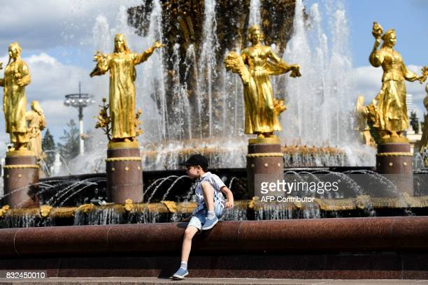 A boy rests on the famous Druzhba Narodov fountain in the AllRussia Exhibition Centre a trade show and amusement park in Moscow on August 16 2017 /...