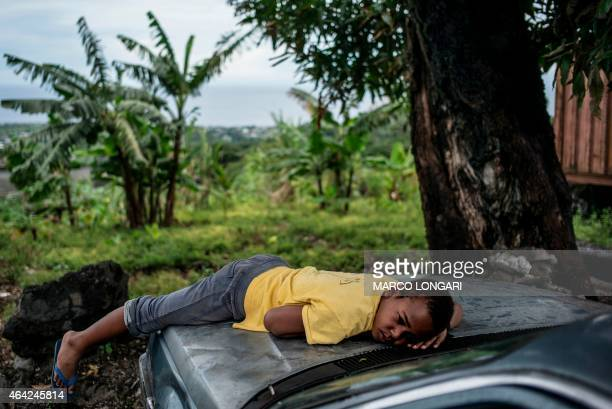 A boy rests on the hood of a wrecked car on a house located on the slopes of the Khartala volcano outside Moroni on February 23 2015 AFP PHOTO/MARCO...