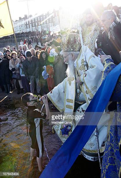 A boy retrieves a cross from the sea that His Eminence Gregorios Greek Orthodox Archbishop of Thyateira and Great Britain threw in as part of the...