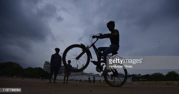 A boy rides a bicycle as clouds hover over Ramilia Ground on April 17 2019 in New Delhi India Strong winds accompanied by light rain lashed the...