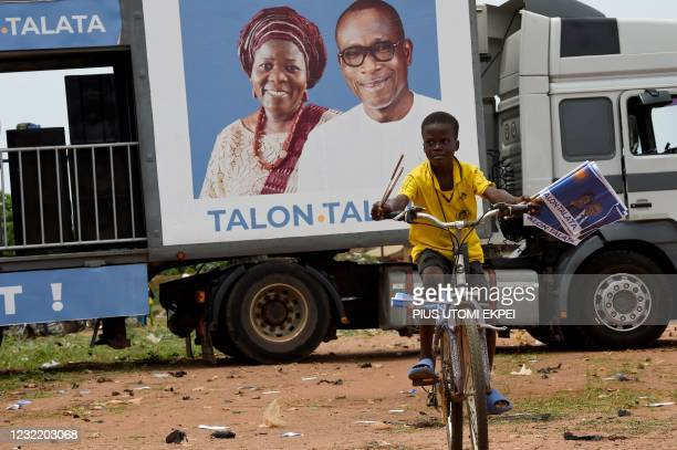 Boy rides a bicycle as he carries flyers of the incumbent President Patrice Talon and running mate Mariam Talata, during a campaign rally at...
