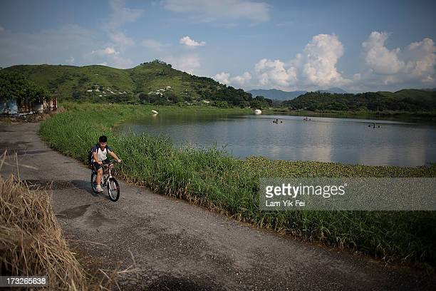A boy rides a bicycle at Ma Tso Lung on July 11 2013 in Hong Kong China The North East New Territories New Development Areas project proposed by...