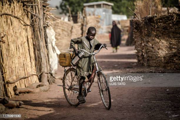 A boy rides a bike near his house at Malkohi refugee camp in Jimeta Adamawa State Nigeria on February 19 four days ahead of the country's General...