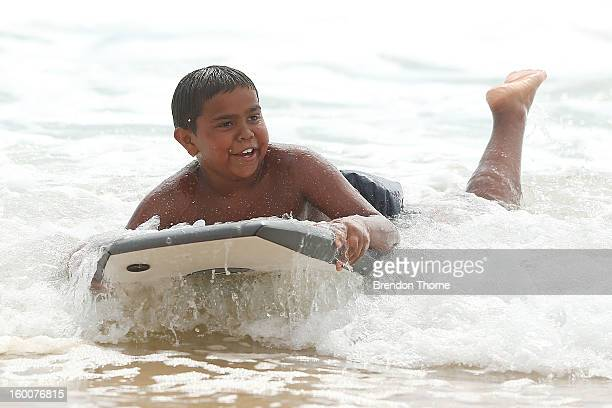 A boy rides a bodyboard as Indigenous children from Brewarrina experience their first trip to the ocean on January 26 2013 in Sydney Australia The...