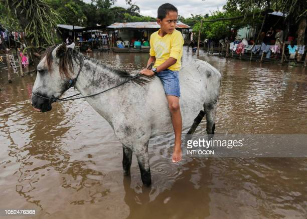 TOPSHOT A boy rides a horse through a flooded area following heavy rains in Tepalon Granada some 80 km east of Managua on October 18 2018
