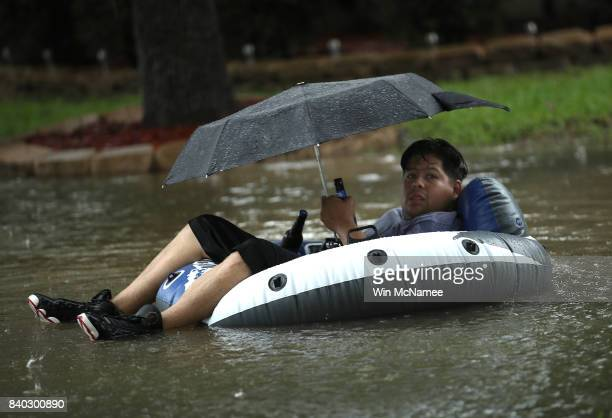 Boy rides a pool float in his front yard after severe flooding following Hurricane Harvey in the Cypresswood Creek subdivision in north Houston...