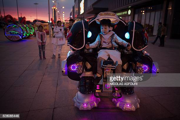 TOPSHOT A boy rides a robot style vehicle outside a shopping mall in Daqing Heilongjiang province on May 2 2016 / AFP / NICOLAS ASFOURI