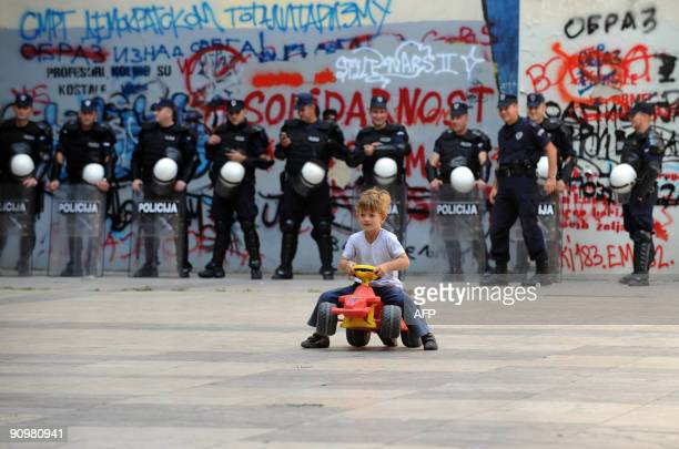 A boy rides a toy car in front of Serbian police officers in downtown Belgrade on September 20 2009 Serb nationalists failed to draw the expected...
