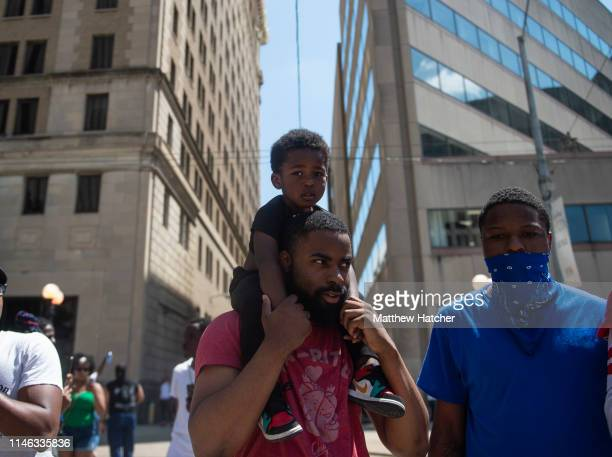A boy rides atop his father's shoulders during a counterprotest to a rally held by the KKK affiliated group Honorable Sacred Knights of Indiana at...