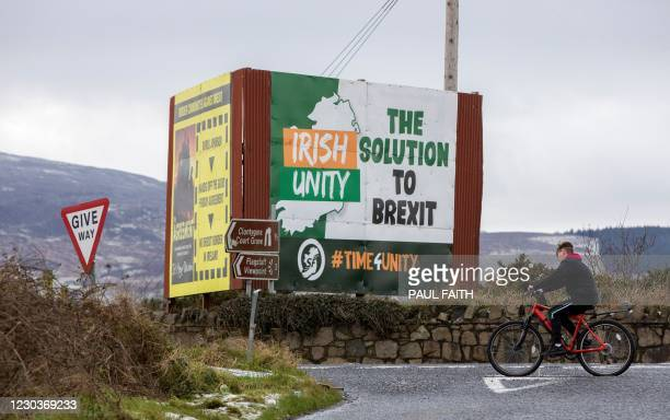Boy rides his bike by a billboard for Irish unification outside Newry, Northern Ireland near the border with Ireland on December 31, 2020. - Britain...