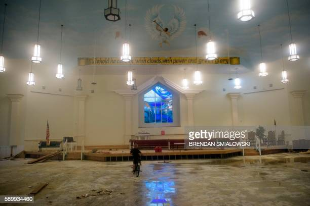 Boy rides his bike inside the flood damaged Life Tabernacle Church on August 15, 2016 in Baton Rouge, Louisiana. Floods ravaged the US state of...