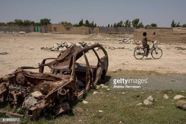 A boy rides his bike past a destroyed car on July 15 2017 in Shadal Bazaar Afghanistan People are slowly returning to the recently liberated area...