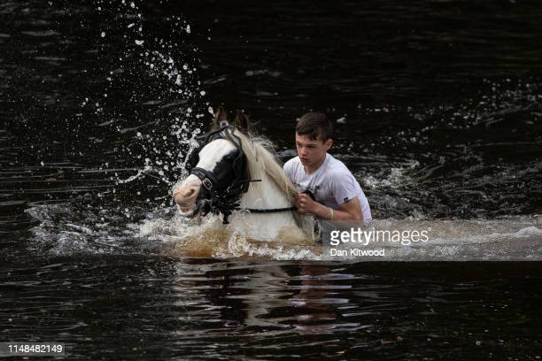 Boy rides his horse in the River Eden during the annual Appleby Horse Fair on June 07, 2019 in Appleby-in-Westmorland, England. The annual gathering...
