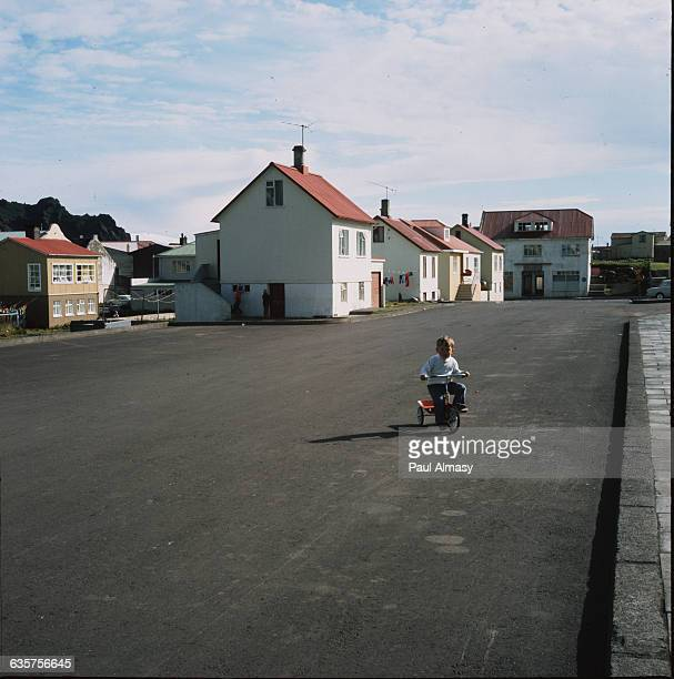 A boy rides his tricycle on a town street in Westman Islands Iceland