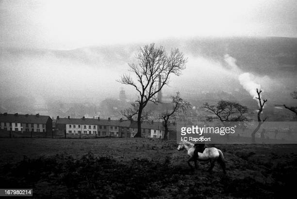 A boy rides his Welsh Pony through the fields near row houses in1966 in a mining town in South Wales