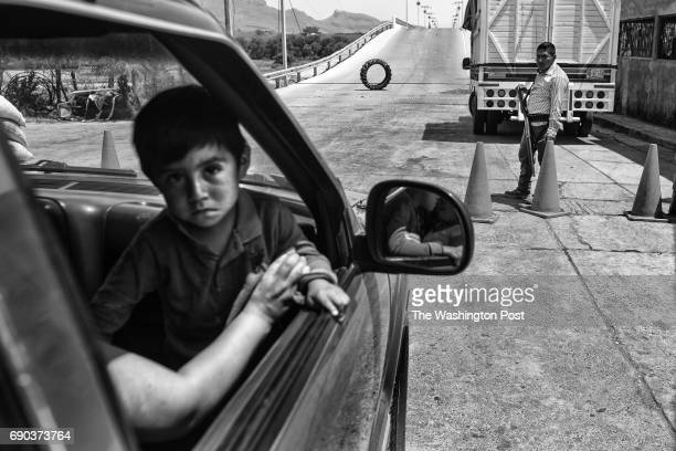 A boy rides in a pickup truck past an auto defensa or self defense group checkpoint in the town of San Miguel Totolapan Mexico on April 27 2017 The...