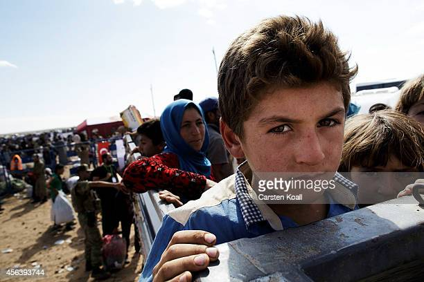A boy rides in a truck with other refugees after crossing from Syria into Turkey September 30 2014 near Suruc Turkey Kurdish troops are engaged in a...
