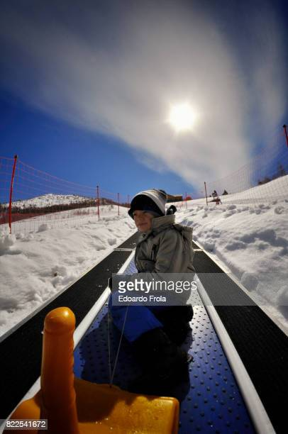 Boy rides 'magic carpet' ski escalator