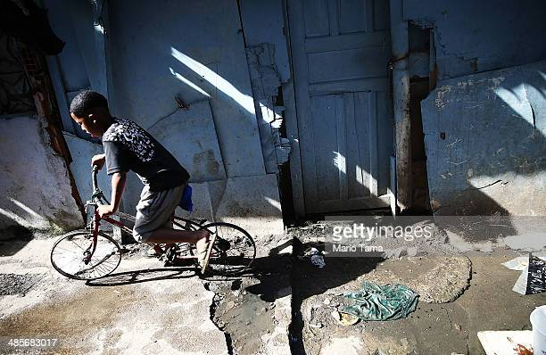A boy rides past on a bike with no tires in an impoverished section of the occupied Complexo da Mare one of the largest 'favela' complexes in Rio on...