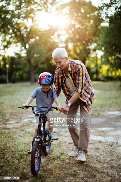 Boy riding a bicycle with   grandpa in the park