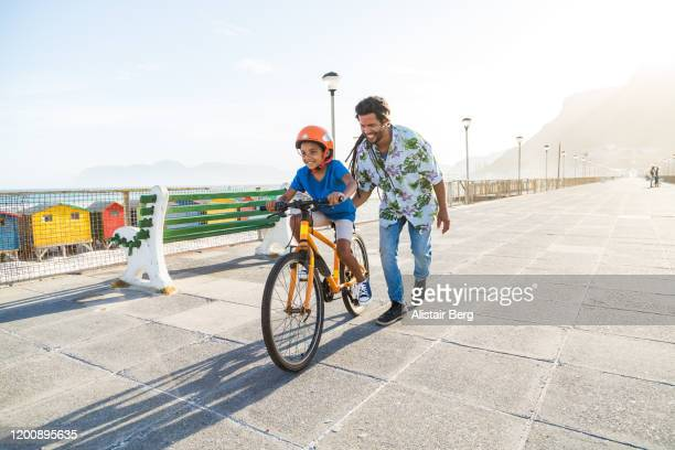 boy riding a bike with his dad - ciclismo - fotografias e filmes do acervo