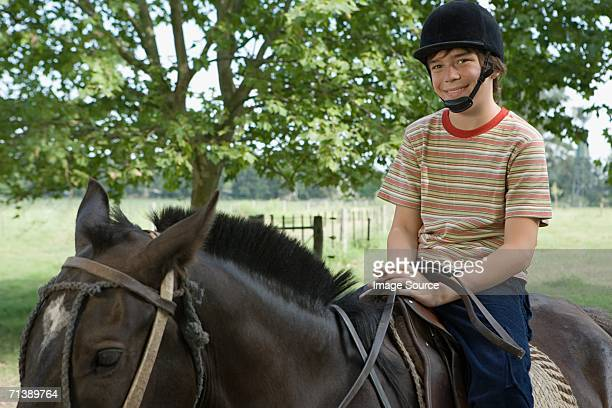 boy riding a horse - equestrian helmet stock pictures, royalty-free photos & images