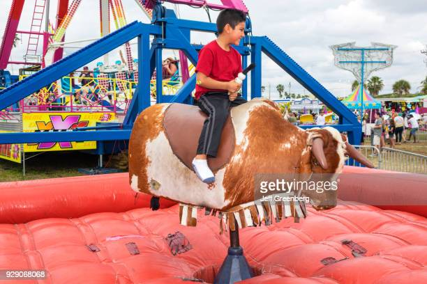 A boy riding a mechanical bull at the Seafood Festival