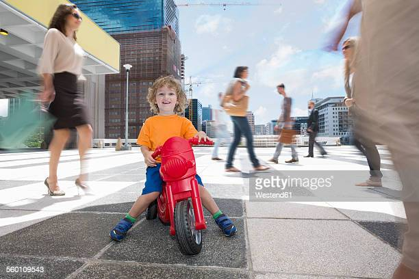 Boy riding a plastic tricycle between a crowd of people in a city