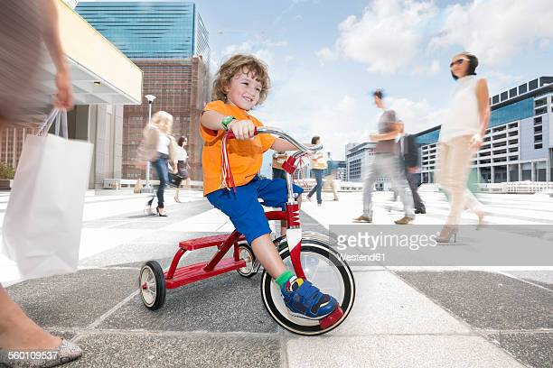Boy riding a tricycle between a crowd of people in a city