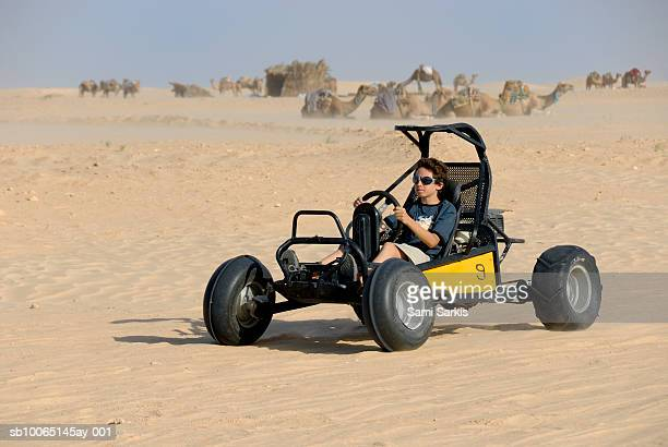 Boy (12-13) riding beach buggy in desert, camels in background