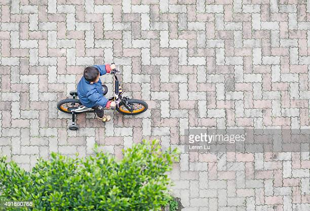 boy riding bicycle alone in courtyard. - paving stone stock pictures, royalty-free photos & images
