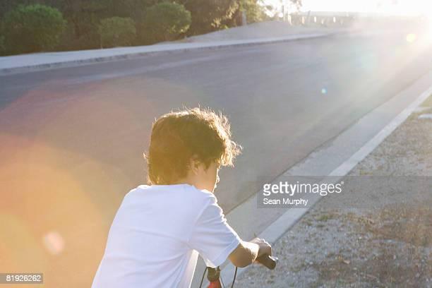boy riding bicycle at dusk