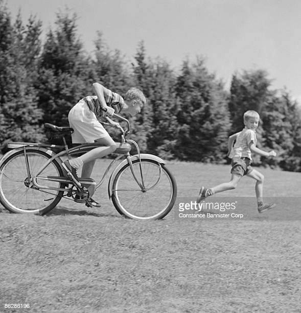 boy riding bicycle chasing running boy - constance bannister stock photos and pictures