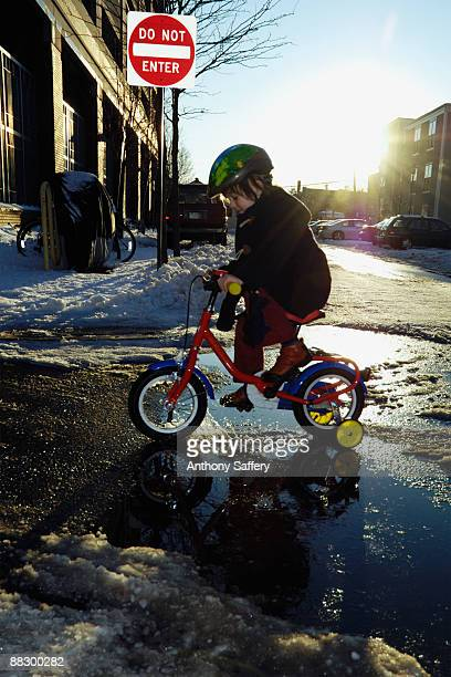 Boy riding bicycle in snowy street