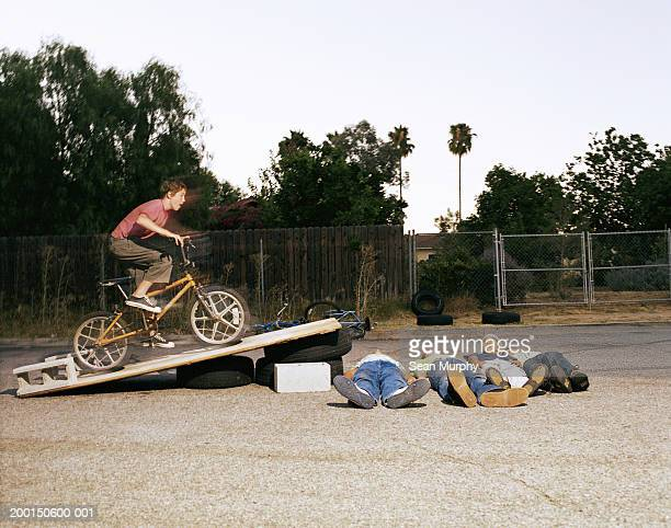 boy (11-15) riding bicycle off jump over friends (blurred motion) - idiots stock pictures, royalty-free photos & images